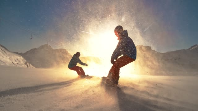 slo mo ts two snowboarders riding down a slope towards the sun - snowboard video stock e b–roll
