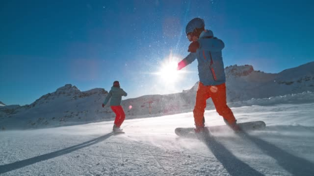 slo mo ts two snowboarders riding down a sunny piste in sunshine flares - snowboard video stock e b–roll