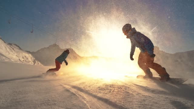 speed ramp two snowboarders riding towards the setting sun - esplorazione video stock e b–roll