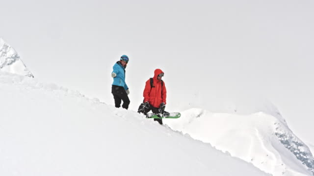 SLO MO Two snowboarders searching for the prefect route in powder snow