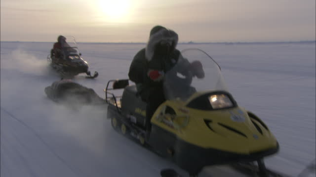 two snowmobile drivers cross a snowy wilderness. - winter sport stock videos & royalty-free footage
