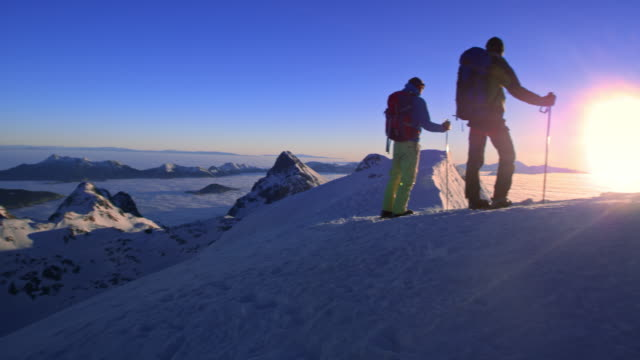 DS Two snowshoers standing on mountain top at sunset