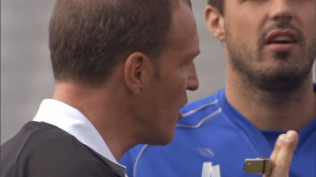 cu two soccer players arguing with referee during soccer game/ sheffield, england - wut stock-videos und b-roll-filmmaterial