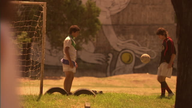 MS, SELECTIVE FOCUS, two soccer players dribbling ball on street side soccer field, Buenos Aires, Argentina