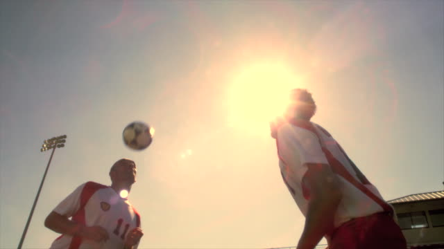 A pair of soccer players head the ball back and forth to one another.
