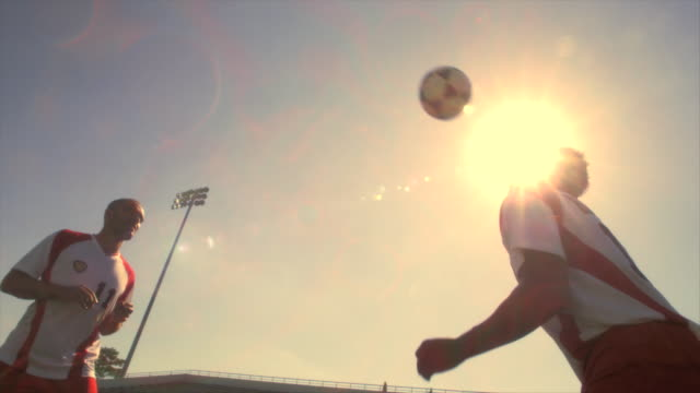 Two soccer players bounce a ball back and forth.
