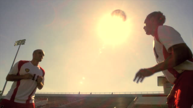 SLO MO. Two soccer teammates heading the ball to each other inside a stadium during practice