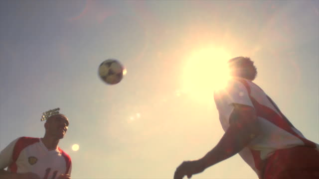 Soccer players head a ball back and forth to each other.
