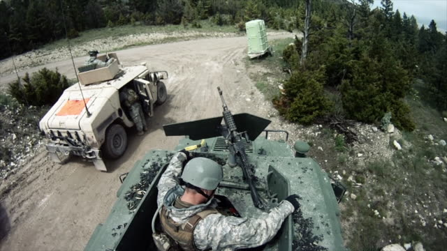 Two Solders trying to fix a gun on their humvee