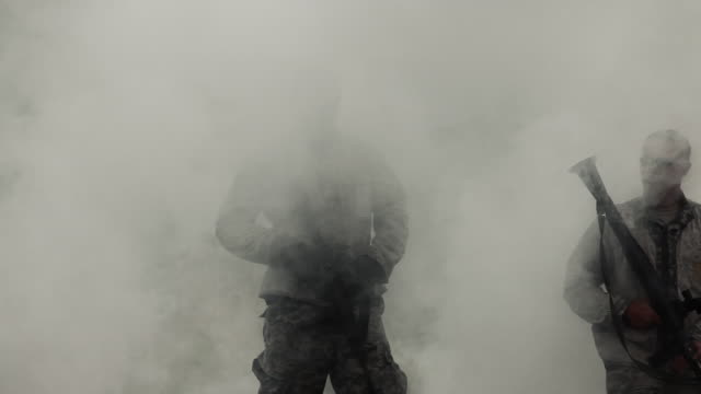 two soldiers appear, walking through a cloud of smoke. - us military stock videos & royalty-free footage