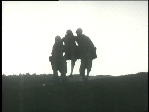 two soldiers carry a wounded soldier down a hill - battle of iwo jima stock videos and b-roll footage