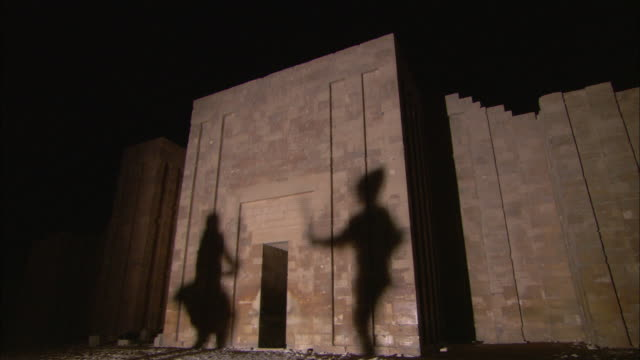 Two soldiers fighting with swords cast their shadows on a stone wall.