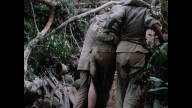 two soldiers help limping wounded solider as wounded troops are evacuated from combat zone near the 17th parallel during the vietnam war in 1966. - produced segment stock videos & royalty-free footage
