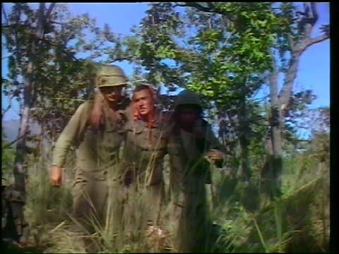 vidéos et rushes de 1965 two soldiers helping third wounded soldier walk thru plants / vietnam war / newsreel - plaie