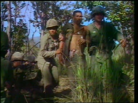 vidéos et rushes de 1965 two soldiers helping wounded black soldier walk thru bushes / vietnam war / newsreel - plaie