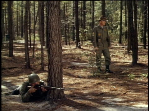 1967 montage two soldiers in the woods, soldier firing his rifle while officer watches / fort campbell, kentucky, united states - fort campbell video stock e b–roll