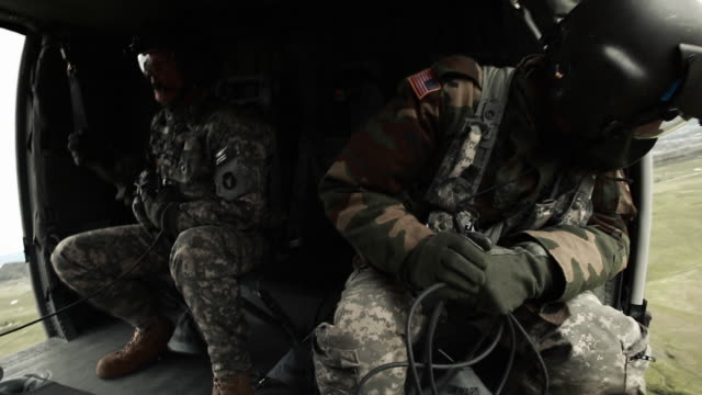 stockvideo's en b-roll-footage met two soldiers inside flying helicopter - militaire training