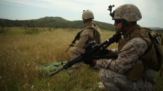 MS Two soldiers kneel and look ahead to vast green hills AUDIO / Camp Pendleton, CA, United States