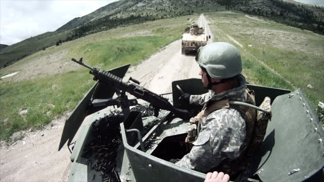 Two soldiers loading a machine gun on a humvee