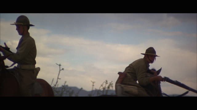 stockvideo's en b-roll-footage met ms two soldiers on horseback, one soldier shooting then falling off his horse - letterbox format