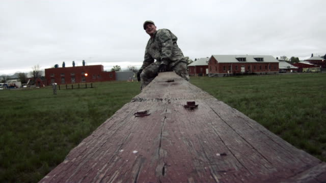 Two soldiers quickly surmounting a wall in training.
