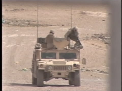 two soldiers stand atop a humvee; one aims his weapon. - al fallujah stock videos & royalty-free footage