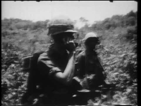 two soldiers standing in bushes, one on telephone / vietnam war - 1966 bildbanksvideor och videomaterial från bakom kulisserna