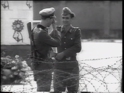 b/w 1961 two soldiers standing talking by barbed wire fence of berlin wall / germany / newsreel - 近衛兵点の映像素材/bロール