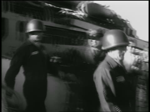 pan two soldiers walking off ship / man takes helmet off one / seattle - 1954 stock videos & royalty-free footage