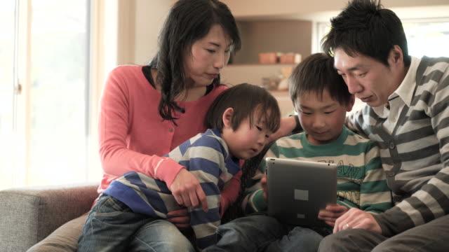 Twee zonen met behulp van een smartphone en digitale tablet pc gebruiken