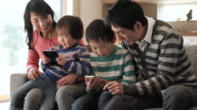 スマートフォンを使用して 2 つの息子、デジタルタブレットを使用している pc - childhood点の映像素材/bロール