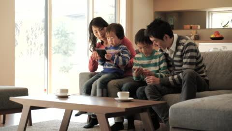 vídeos y material grabado en eventos de stock de dos hijos usando un teléfono inteligente y tableta digital pc con - cuatro personas