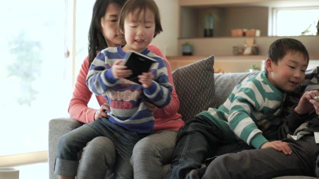 stockvideo's en b-roll-footage met twee zonen met behulp van een smartphone en digitale tablet pc gebruiken - tablet pc