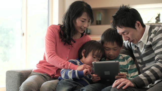two sons using a smartphone and using digital tablet pc - joy stock videos & royalty-free footage