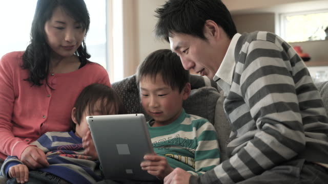 two sons using a smartphone and using digital tablet pc - only japanese stock videos & royalty-free footage