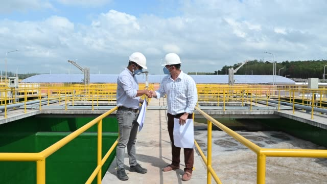 Two South East Asian Engineers discussing and talking on blueprint at Sewage Treatment Plant