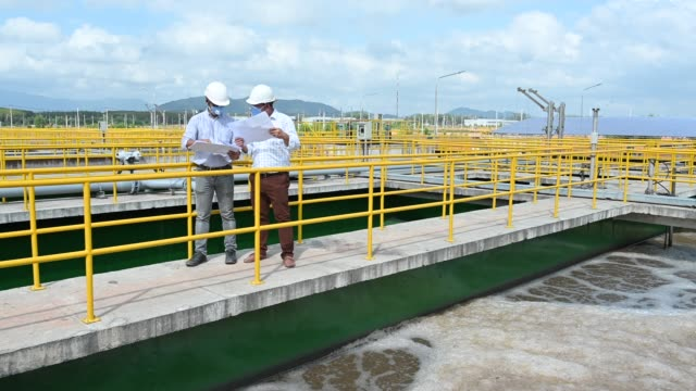 two south east asian engineers discussing and talking on blueprint at sewage treatment plant - southeast asia stock videos & royalty-free footage