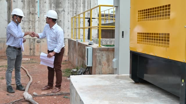 two south east asian engineers discussing and talking on blueprint at construction site - technician stock videos & royalty-free footage