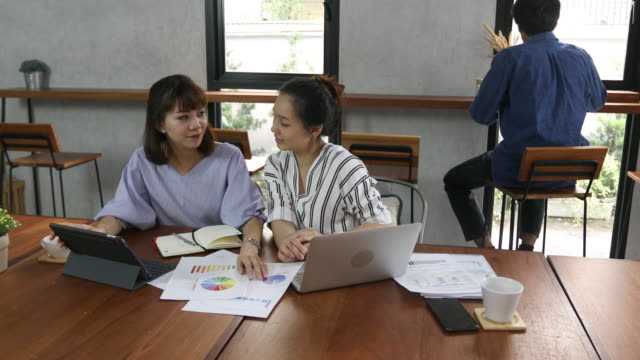 two southeast asia woman talking and working in cafe - vietnam stock videos & royalty-free footage