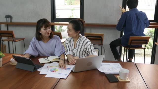 stockvideo's en b-roll-footage met twee zuidoost-azië vrouw praten en werken in café - vietnam