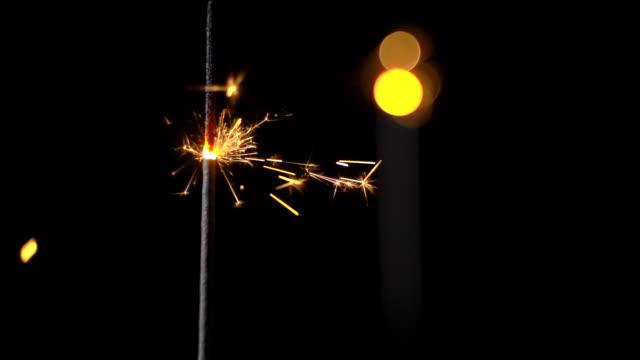 スローモーションで燃える黒い背景に2つのスパークラー、1つは前景、1つは背景に、焦点が落ち、ボケ味 - 超新星点の映像素材/bロール