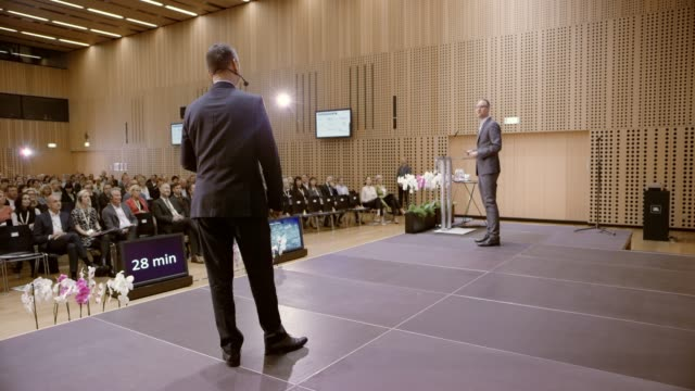 stockvideo's en b-roll-footage met twee luidsprekers op het podium in de conference hall - conferentie