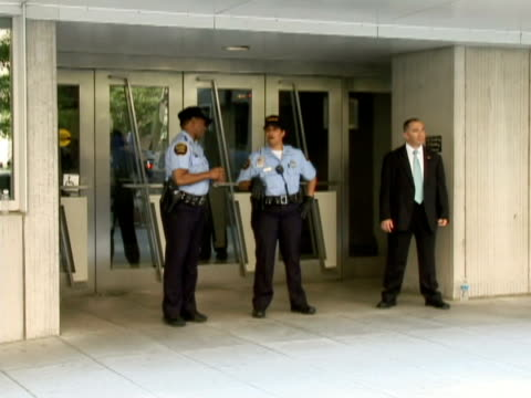 vídeos de stock, filmes e b-roll de two special police officers and security personnel standing outside the imf / washington dc, united states / audio - traje completo