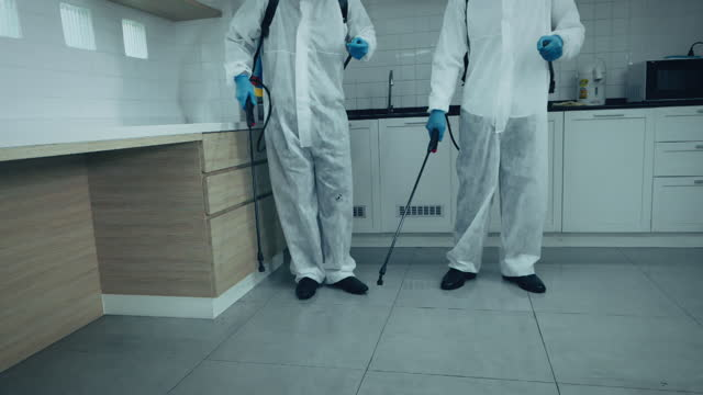 vídeos de stock e filmes b-roll de two specialists males in protective suit and face mask spraying for disinfection in the office and breeding ground for pathogens, 4k resolution, covid-19 effects, slow motion. - epidemiologia