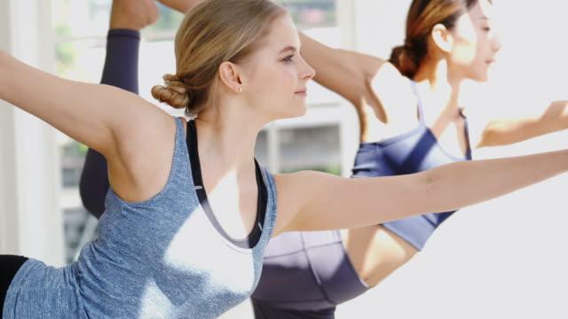 two sport women practicing yoga together - allenamento a corpo libero video stock e b–roll