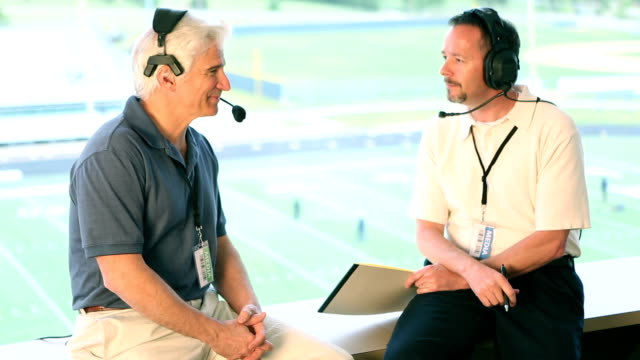 two sports announcers talking about pregame in booth. - american football sport stock videos & royalty-free footage