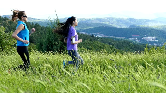 two sportswomen jogging in nature-slow motion - arm band stock videos & royalty-free footage