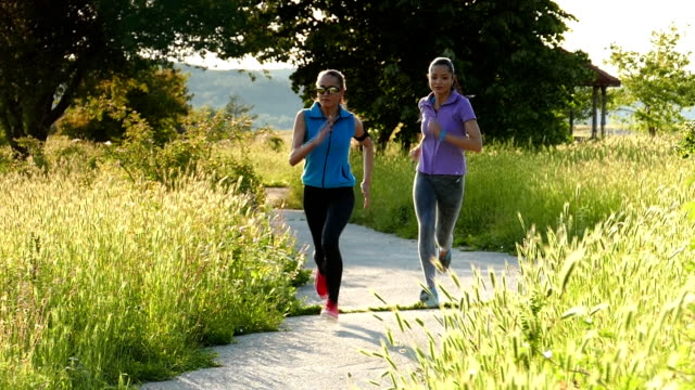 two sportswomen jogging in the field-slow motion - arm band stock videos & royalty-free footage