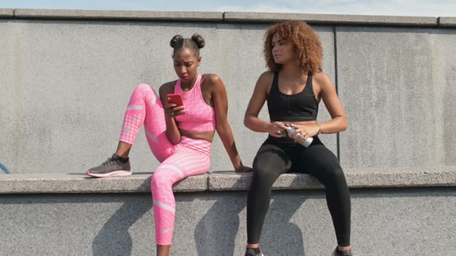 two sporty women relaxing after work out - bottle stock videos & royalty-free footage