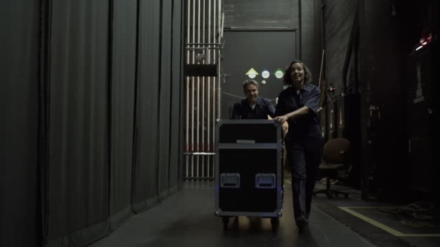 Two stage workers wheeling equipment trolley towards camera, backstage